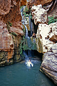 Dave and Angelina jumping in, Wolf in Elves Chasm which is a tributary canyon area to the Colorado river which rafters hike up during river trips, Grand Canyon, Arizona.  Whit Richardson / Aurora Photos