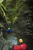 Davis Creek, South of Mount Rainier, WA. Canyoning is a new sport that consists in travelling down river canyons by walking, gliding, climbing, rappelling abseiling, swimming or jumping. Rob Cobb blue, and Joe Budgen red, wade down a wet section of Davis