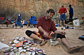 Jim Crossland smashing cans to make them smaller and easier to pack out during 18 day raft trip, Grand Canyon, Arizona, USA.