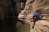 Jim Crossland traversing on rock above pool in Elves Chasm, Grand Canyon, Arizona, USA.