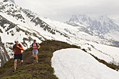 Two people run on a ridge top on a cloudy day in the Alps near Chamonix, France.