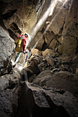 Rob Eavis descends into a daylight lit underground chamber in the White Mountains on the island of Crete.