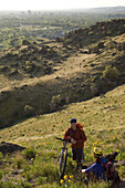 Jake Hawkes and Lorien Lightfield take a break while mountain biking in the Boise Foothills overlooking Boise, Idaho. The image shows the couple in a scenic area of the foothills with a view of the city in the background.