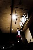 Wide shot of a basketball player slamming a ball.