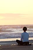 Woman listening to headphones amid beach grass, dunes and sunshine along Oregon coast near Lincoln City - Heather Pfeiffer.