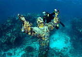 Scuba diver, Daniel Brown pauses next to the Statue of Christ of the Abyss, located on a coral reef in the Florida Keys National Marine Sanctuary, Key Largo, Florida.