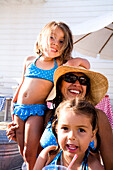 Mom and two little girls smile for the camera at a pool party.