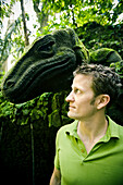 Aaron Gulley faces a sculpture of a giant Komodo Dragon covered in moss at the Holy Bathing Temple along the sacred Monkey Forest Road in Ubud, Bali Indonesia.