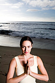 A women at the beach performing yoga and meditation. releasecode: 20071030-LauraSparaco