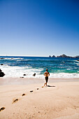 A swimmer walks out to the water in Cabo San Lucas, Mexico  releasecode: 20071103-SamWells.jpg
