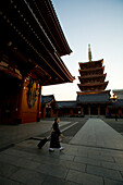 A Japanese woman walks near a traditional temple in Tokyo, Japan. Many Japanese people do not believe in one religion exclusively, instead they incorporate facets of several religions into their lives.