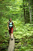 Zoom blur image of Claudine Safar hiking along a wooden boardwalk on the approach hike in to the Wild River crags near Gilead, ME