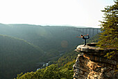 Sarah Chouinard enjoys a late afternoon yoga session standing bow pose, atop the Bosnian Buttress along the rim of the New River Gorge near Fayetteville, WV