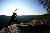 Sarah Chouinard enjoys a late afternoon yoga session pose : Side Angle - parsvakonasana, atop the Bosnian Buttress along the rim of the New River Gorge near Fayetteville, WV