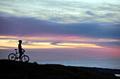 A mountain biker pauses for a moment to enjoy a sunset over the Pacific Ocean.