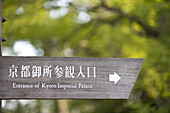 Sign for former Imperial Palace grounds now a park, written in Japanese and English with trees in background in Kyoto, Japan.