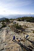 Anna Romer and Jose Azel hike with their daughter Sasha Azel to reach the peak of Mount Kearsarge, on the eastern fringe of the White Mountains of New Hampshire, on a sunny fall day.