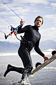 Traveler Terpening carries his kiteboard as he heads out for a kitesurfing session in Homer, Alaska on July 21, 2007.
