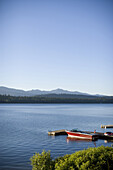 A red waterski boat is docked on a beautiful morning on Payette Lake near McCall Idaho