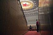 A Chinese attendant in the Great Hall of the People, near a ceiling decoration of a giant red star, during a session of the National People's Congress, China's Parliament.