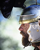 Close up side view portrait of a man wearing a metal helmet with headdress, looking like a medieval warrior. California. releasecode: rrk_mr164