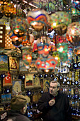 Istanbul, Turkey - January, 2008: Two men drinking tea in a souvenir shop. The Grand Bazaar in Istanbul, Turkey is a centuries old covered market place made up of a maze of several kilometers of chaotic lanes housing over 4000 shops selling almost everyth