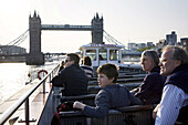 LONDON, UNITED KINGDOM - May 14:  Passengers on a ferry on the Thames River in London.  Tower Bridge rises in the background.