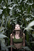 A beautiful young woman stretches towards the sky in the middle of a New Hampshire corn field.