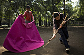 Bullfighting students play the role of the bullfighter and bull as they practice in a public park in Mexico City, September 11, 2008.