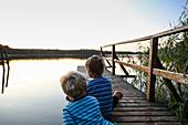 Two boys sitting on a jetty at a lake in dusk, Schorfheide-Chorin Biosphere Reserve, Neudorf, Friedenfelde, Uckermark, Brandenburg, Germany