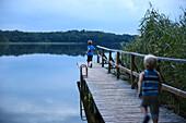 Two boys running along a jetty at a lake, Schorfheide-Chorin Biosphere Reserve, Neudorf, Friedenfelde, Uckermark, Brandenburg, Germany