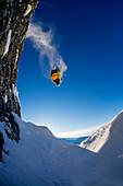 Skifahrer macht Backflip über hohes Kliff und steht kopfüber in der Luft, Hochfügen, Zillertal, Österreich