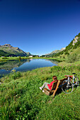 Cyclist resting on a bench with view over Inn river to Sils-Baselgia, Sils, Upper Engadin, Engadin, Canton of Graubuenden, Switzerland