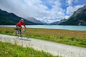 Woman cycling along Lake Silvaplana, Upper Engadin, Engadin, Canton of Graubuenden, Switzerland