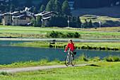 Woman cycling along Lake Champfer, Silvaplana, Upper Engadin, Canton of Graubuenden, Switzerland