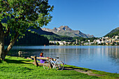 Cyclist resting on a bench at Lake St. Moritz, St. Moritz, Upper Engadin, Kanton of Graubuenden, Switzerland