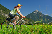 Woman cycling along Inn cycle route, Tschirgant in background, Mils, Tyrol, Austria