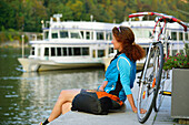 Cyclist resting at Danube riverbank, Passau, Lower Bavaria, Germany