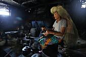 Ivatan woman cooking inside an old kitchen in Chavayan village, wearing a typical straw wig, Sabtang Island, Batanes, Philippines, Asia