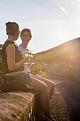 Two young women enjoying white wine on a wall along the Stein-Wein-Pfad trail in vineyard above Weingut am Stein winery, Wuerzburg, Franconia, Bavaria, Germany
