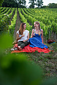 Two young women enjoying a glass of white wine in the vineyard above Weingut am Stein winery (MR), Wuerzburg, Franconia, Bavaria, Germany