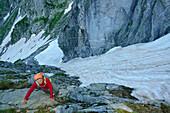 Woman climbing through rocky terrain, snowgully in background, Sentiero Roma, Bergell range, Lombardy, Italy