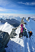 Woman standing at southern ridge of Gran Paradiso, Gran Paradiso, Gran Paradiso Nationalpark, Graian Alps range, valley of Aosta, Aosta, Italy