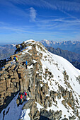 Several persons climbing on ridge to Gran Paradiso, Mont Blanc in background, Gran Paradiso, Gran Paradiso Nationalpark, Graian Alps range, valley of Aosta, Aosta, Italy