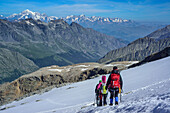 Several persons descending on glacier from Gran Paradiso, Mont Blanc in background, Gran Paradiso, Gran Paradiso Nationalpark, Graian Alps range, valley of Aosta, Aosta, Italy