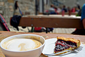 Cup of coffee and cake at terrace of Rifugio Vittorio Emanuele II, Gran Paradiso, Gran Paradiso Nationalpark, Graian Alps range, valley of Aosta, Aosta, Italy