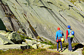 Two people with climbing gear approaching a rock face, Azalee Beach, Grimsel pass, Bernese Oberland, Switzerland
