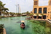 Dhows cruise around the Madinat Jumeirah Hotel with Burj Al Arab in the background, Dubai, United Arab Emirates, Middle East