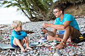 Father and son (4 years) cooking at beach, Naesgaard, Falster, Denmark
