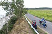 Family cycling along coastal road, Rytsebaek, Island Mon, Denmark